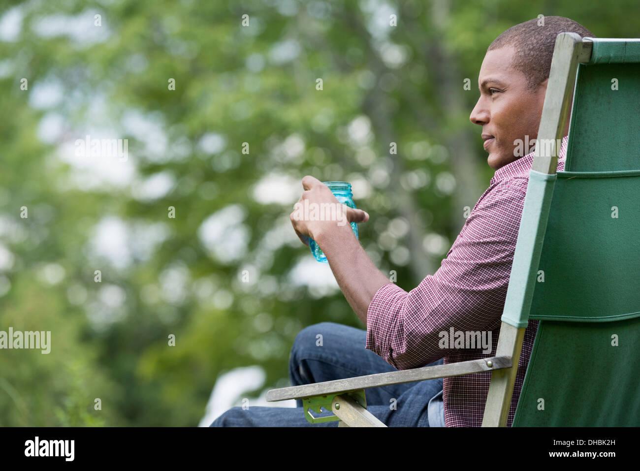Un homme assis sur une chaise dans un jardin, se détendre. Photo Stock