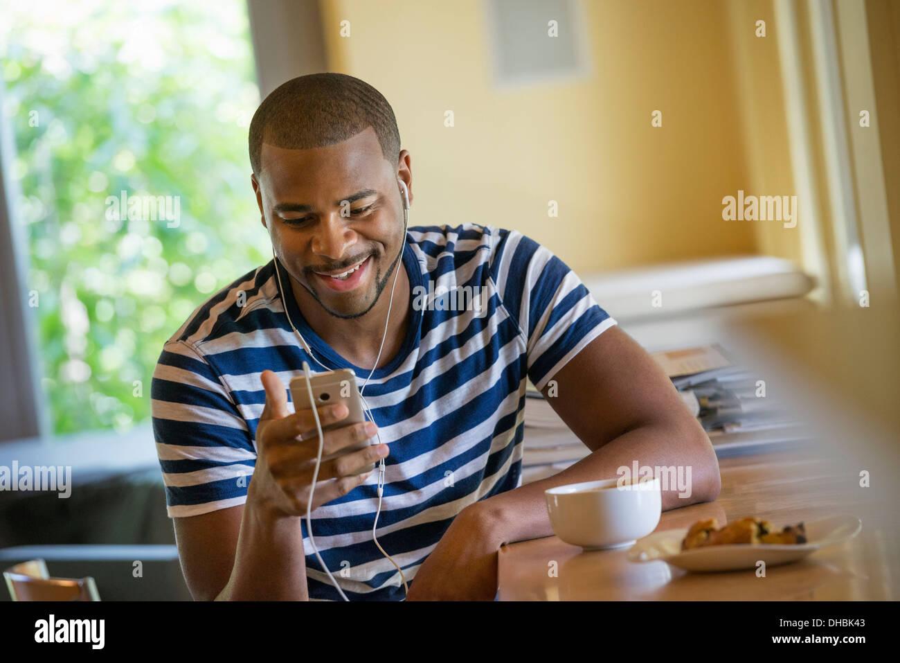 Un homme à l'aide d'un téléphone intelligent, ou lecteur de musique personnel, portant des écouteurs. Photo Stock
