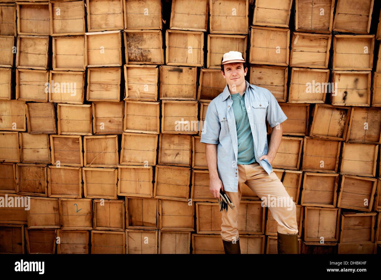 Un fermier debout devant un mur de caisses en bois empilées pour produire. Photo Stock
