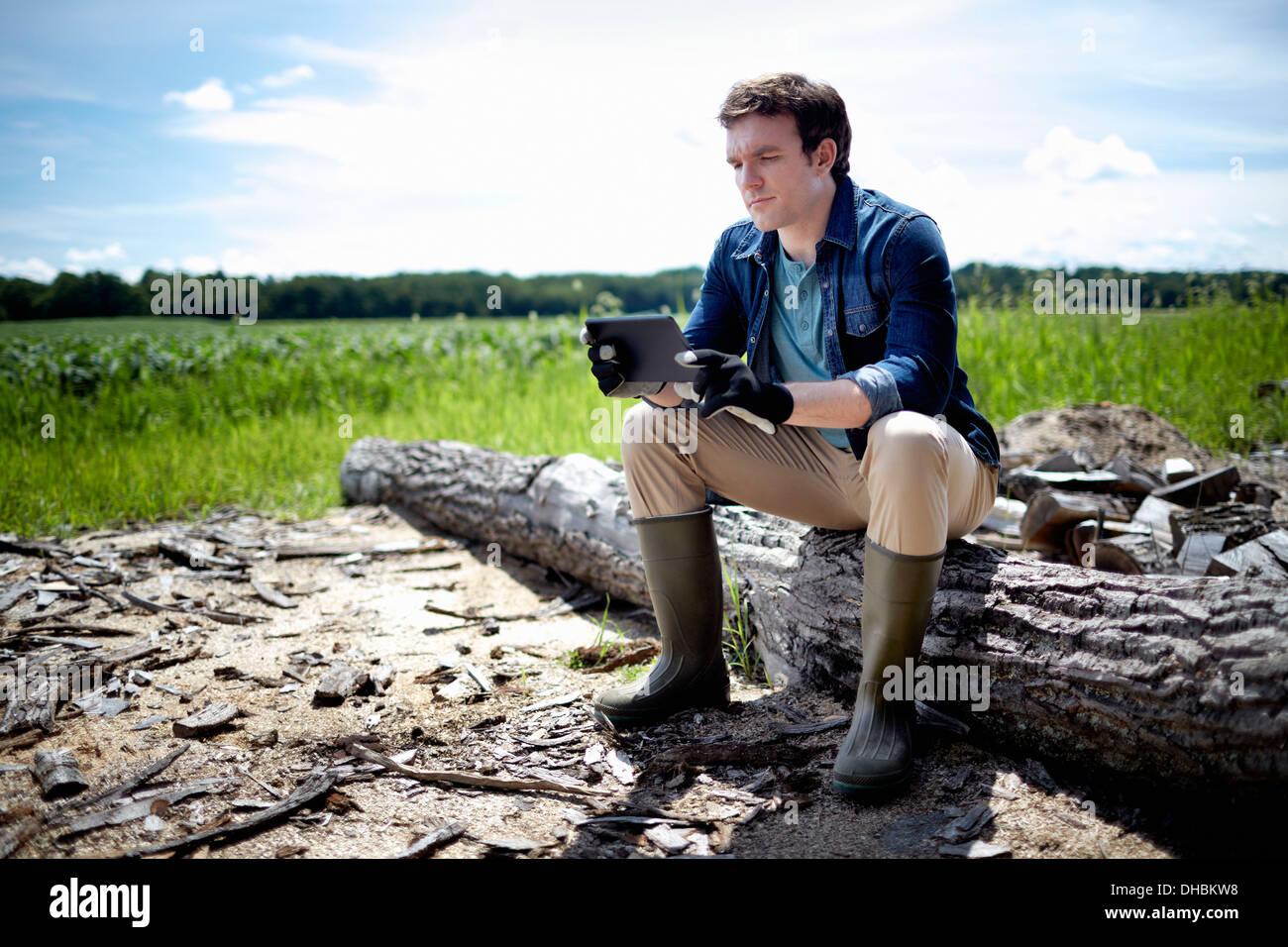 Un fermier assis à l'aide d'un ordinateur tablette en plein air dans un champ de cultures Photo Stock