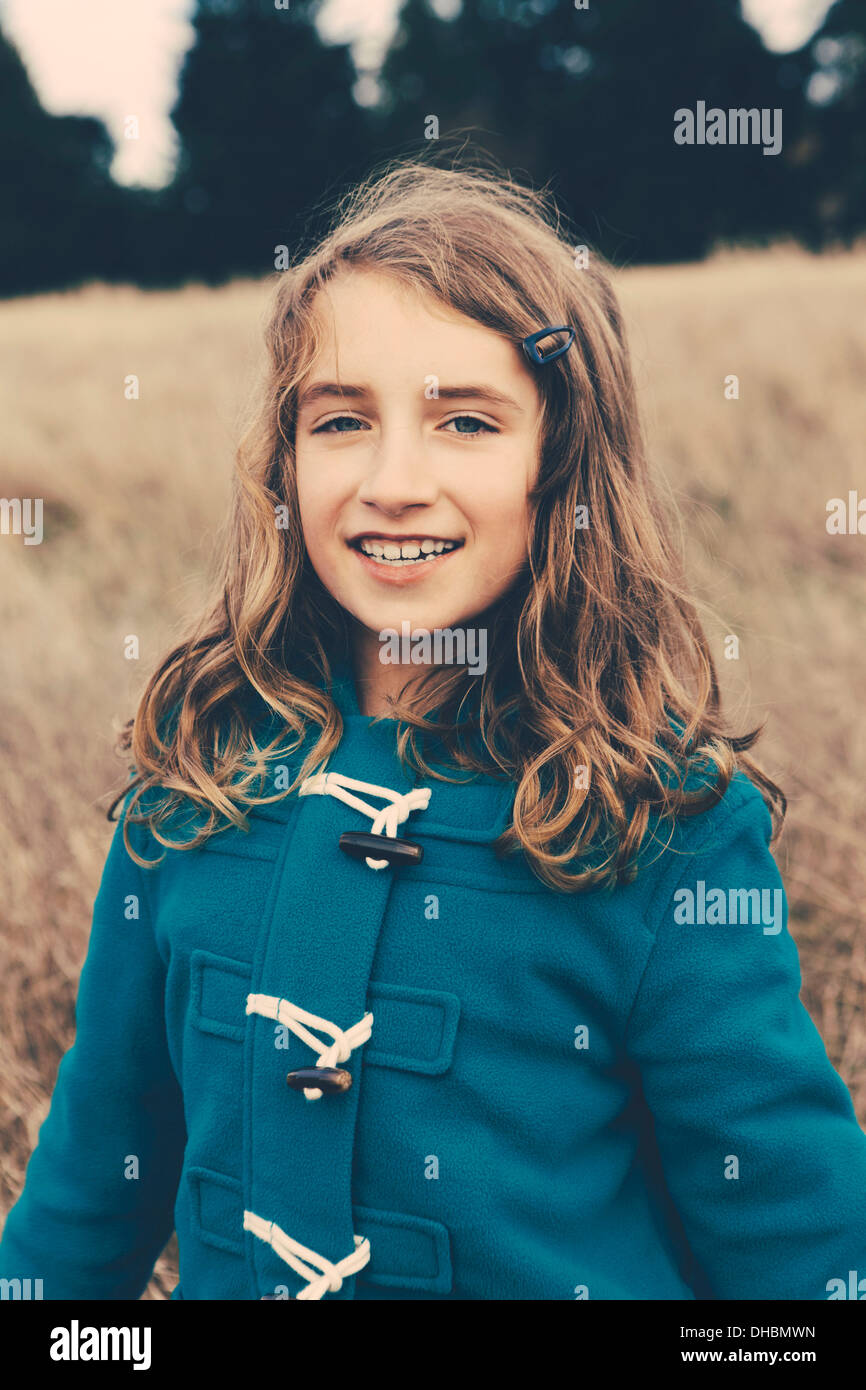 Une jeune fille de neuf ans, dans un duffle coat Bleu, souriant à la caméra. Photo Stock