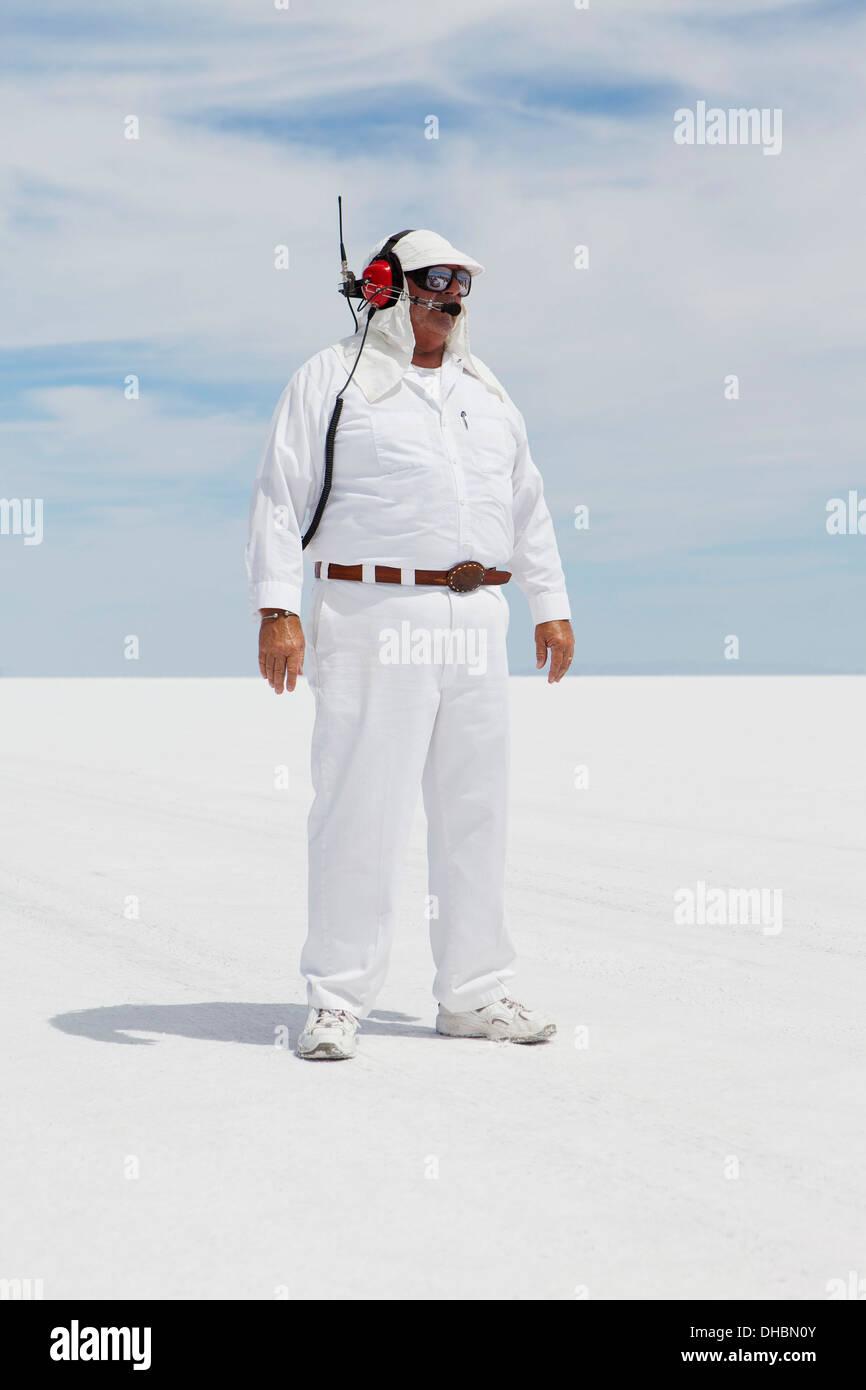 Un homme en combinaisons blanches, avec un casque radio, un chronométreur officiel de la course sur une voiture de course, vitesse 7. Photo Stock