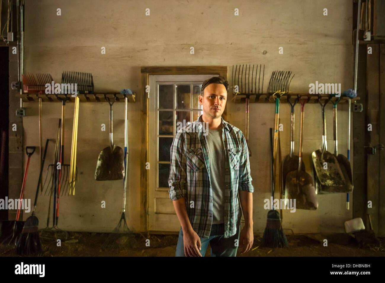 Une ferme biologique dans les Catskills. Un homme debout dans une grange avec de l'équipement entreposé autour des murs. Photo Stock