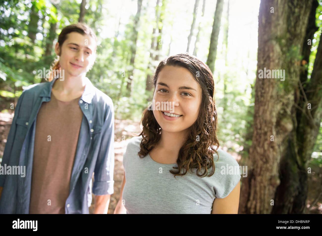 Deux personnes, une jeune femme et l'homme, marchant côte à côte dans les bois. Photo Stock