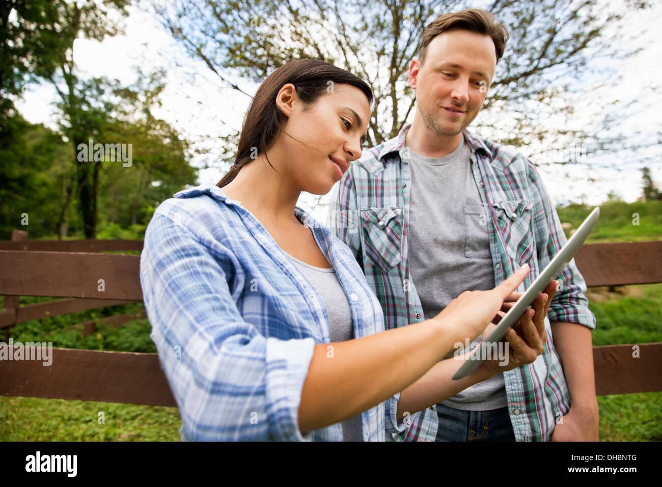 Une ferme biologique dans les Catskills. Deux personnes à la recherche à l'écran d'une tablette numérique. Photo Stock