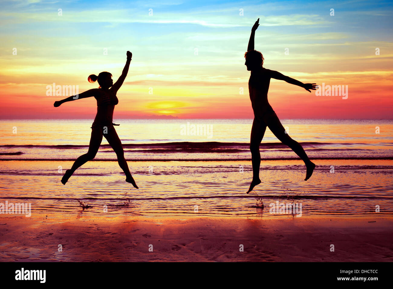 Bonheur, couple jumping on the beach Photo Stock