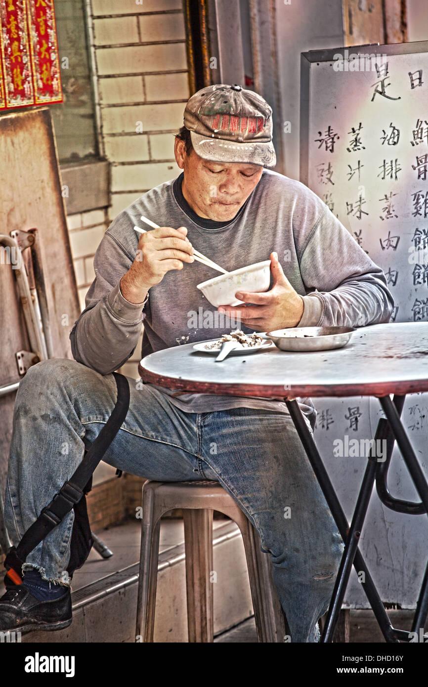 Un homme de 40 à 50 ans manger du riz dans un restaurant à Hong Kong. L'image est une photo couleur en format portrait. Photo Stock