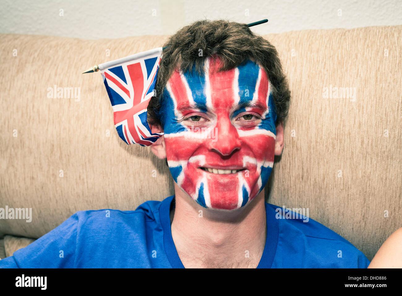 Portrait de l'homme drôle avec drapeau anglais peint sur son visage. Photo Stock