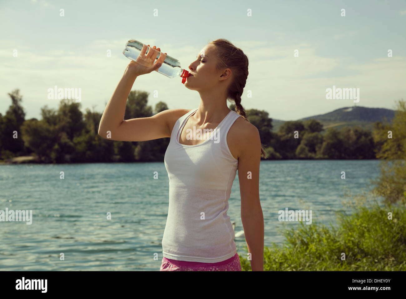 Young female jogger de boire de l'eau en bouteille Photo Stock