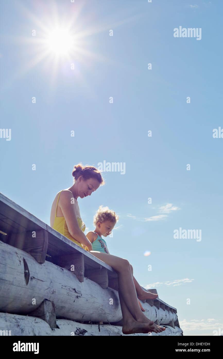 Mother and Daughter sitting on pier, Utvalnas, Gavle, Suède Banque D'Images