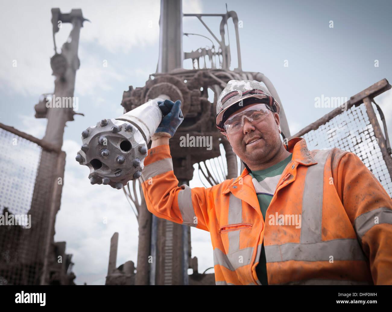 Portrait de l'appareil de forage worker in hard hat et vêtements Photo Stock
