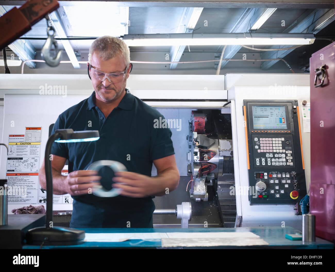 Engineer inspecting metal partie en usine Banque D'Images