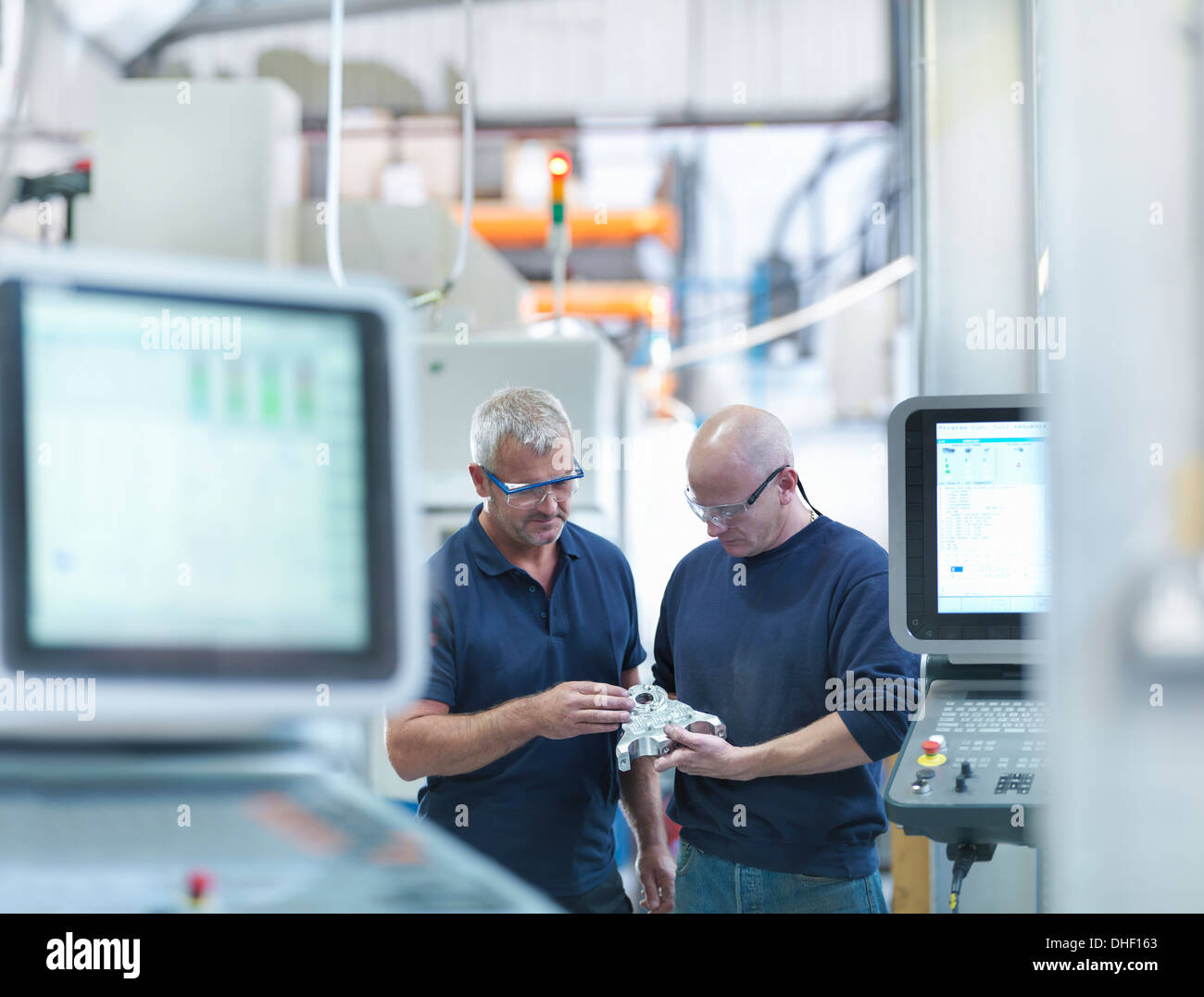 Engineers inspecting complex metal component in factory Photo Stock