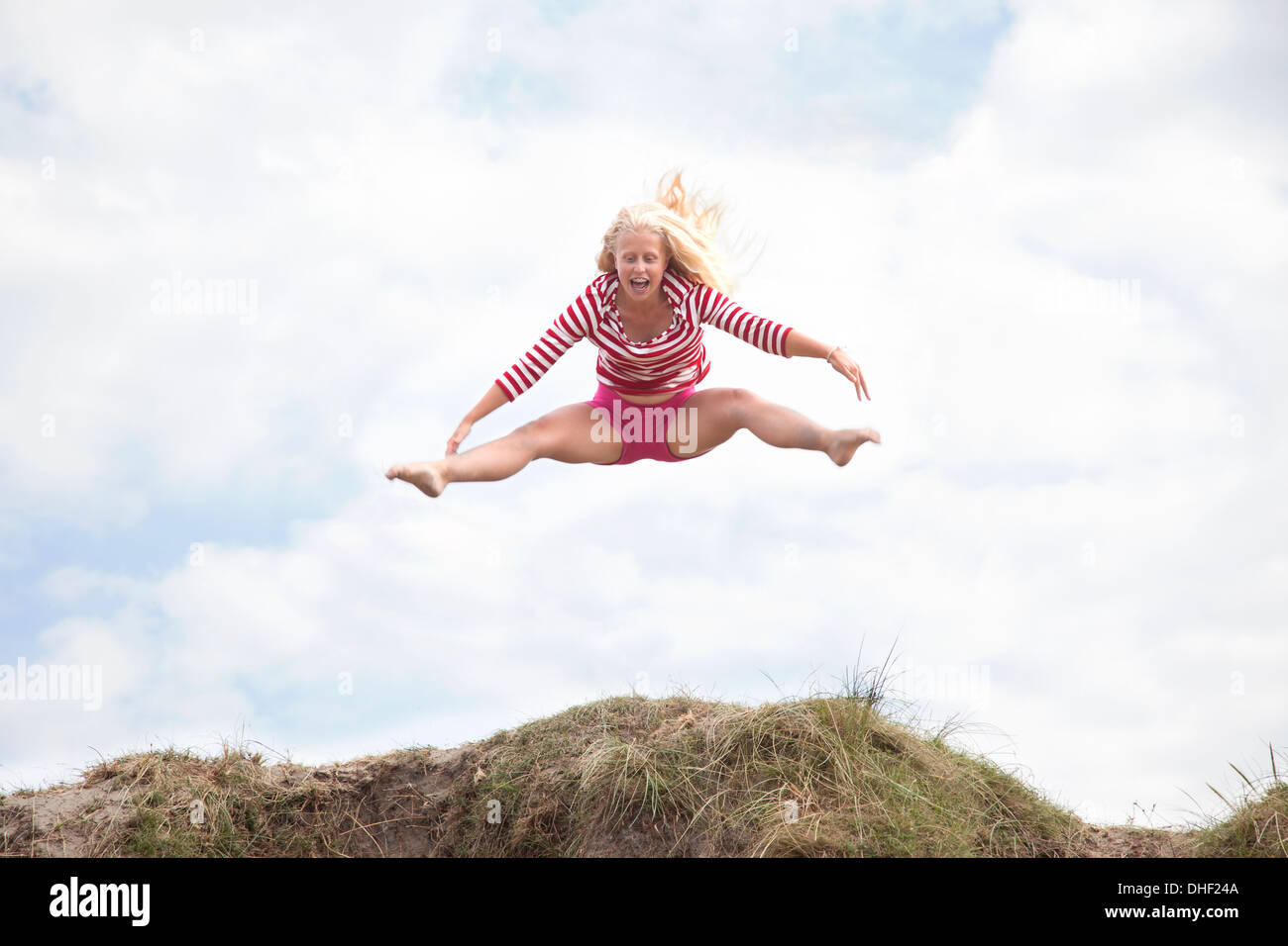 Teenage girl leaping mid air avec jambes, Pays de Galles, Royaume-Uni Photo Stock