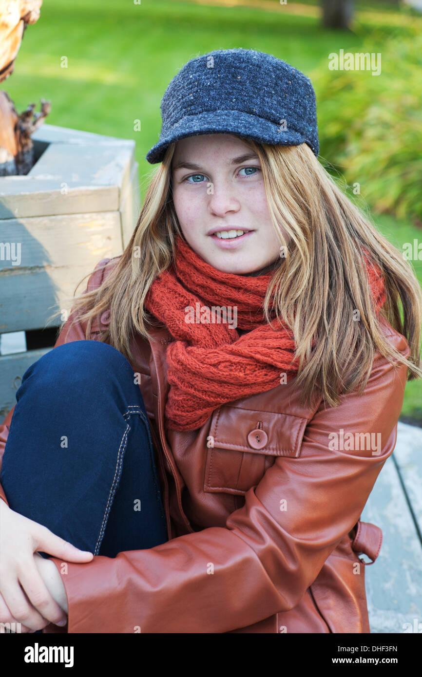 4d3095b1cea51 Jeune fille assise sur un banc à l extérieur.Elle est de porter un chapeau  et blouson de cuir.