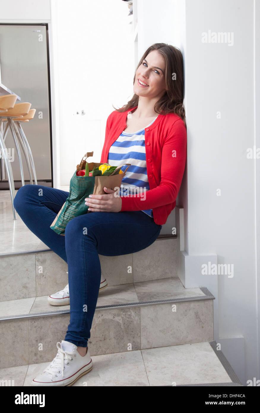 Jeune femme assise sur l'étape du sac à provisions avec cuisine Photo Stock