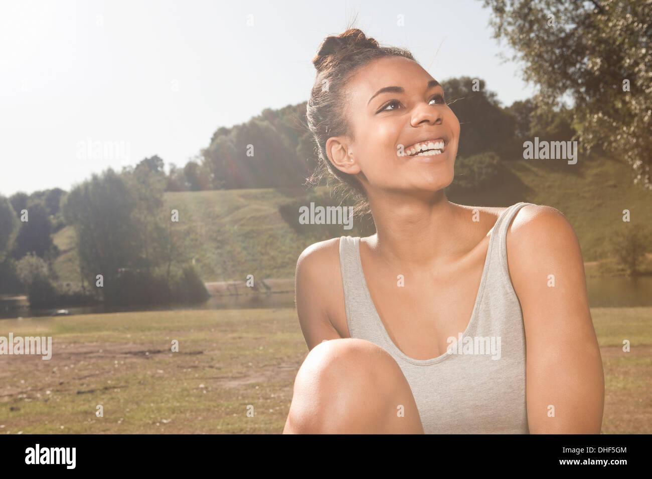 Jeune femme heureuse dans la lumière du soleil dans un parc Photo Stock