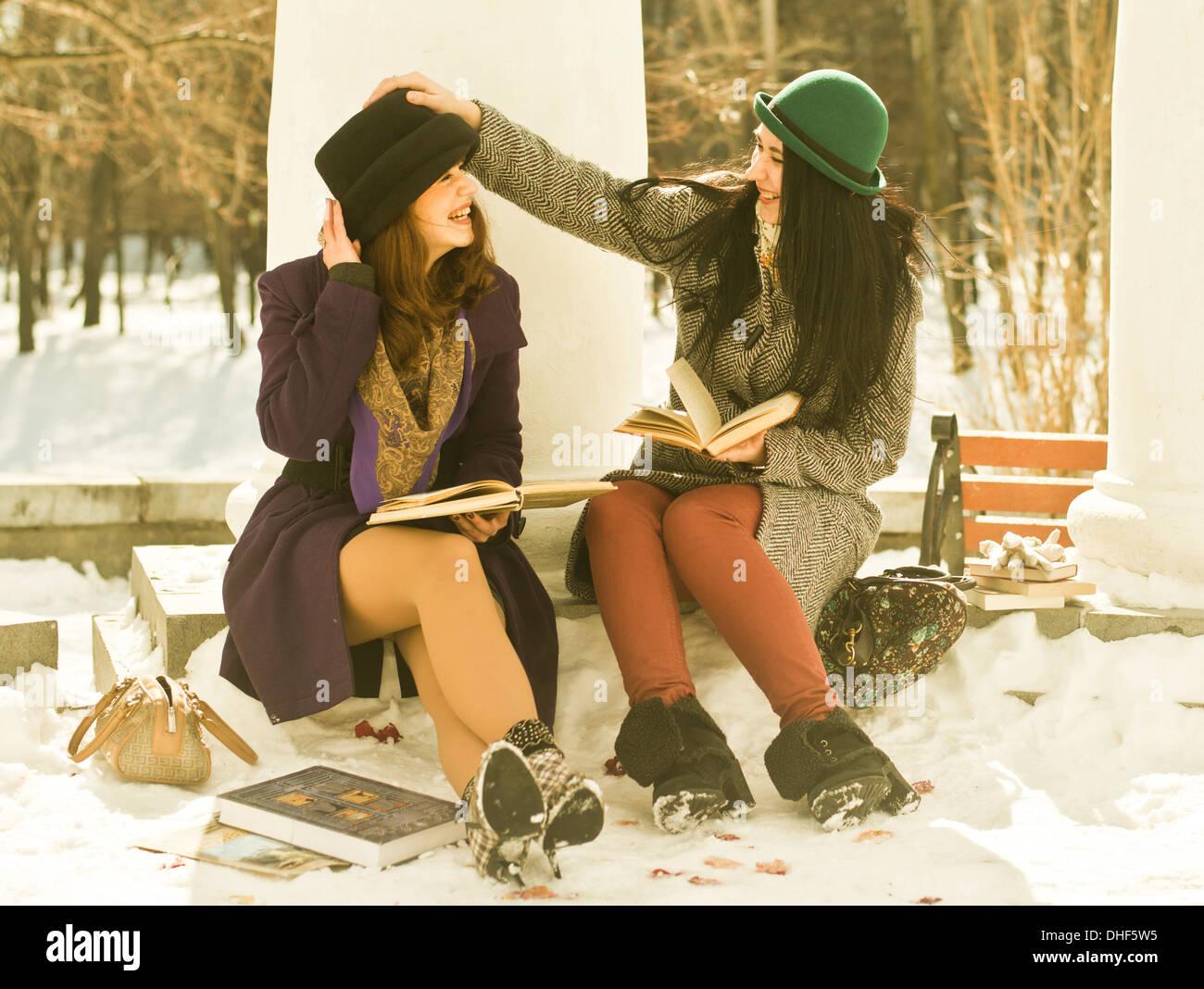 Deux jeunes femmes avec des livres sur banc de parc dans la neige Photo Stock