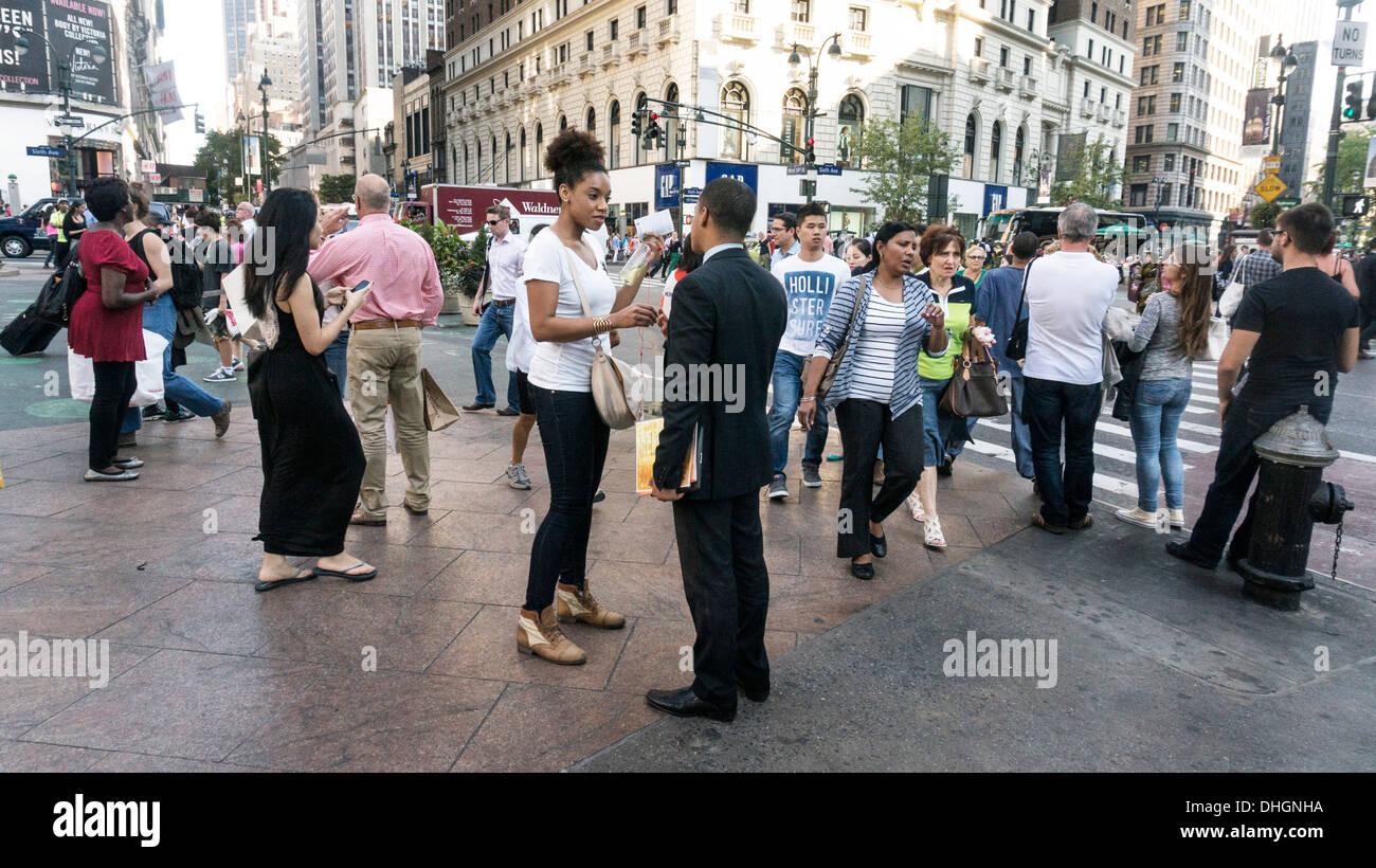 Foule multiethnique des piétons et des mains dans toutes les directions comme le changement des feux de l'intersection de la 34e rue et de la Sixième Avenue Photo Stock