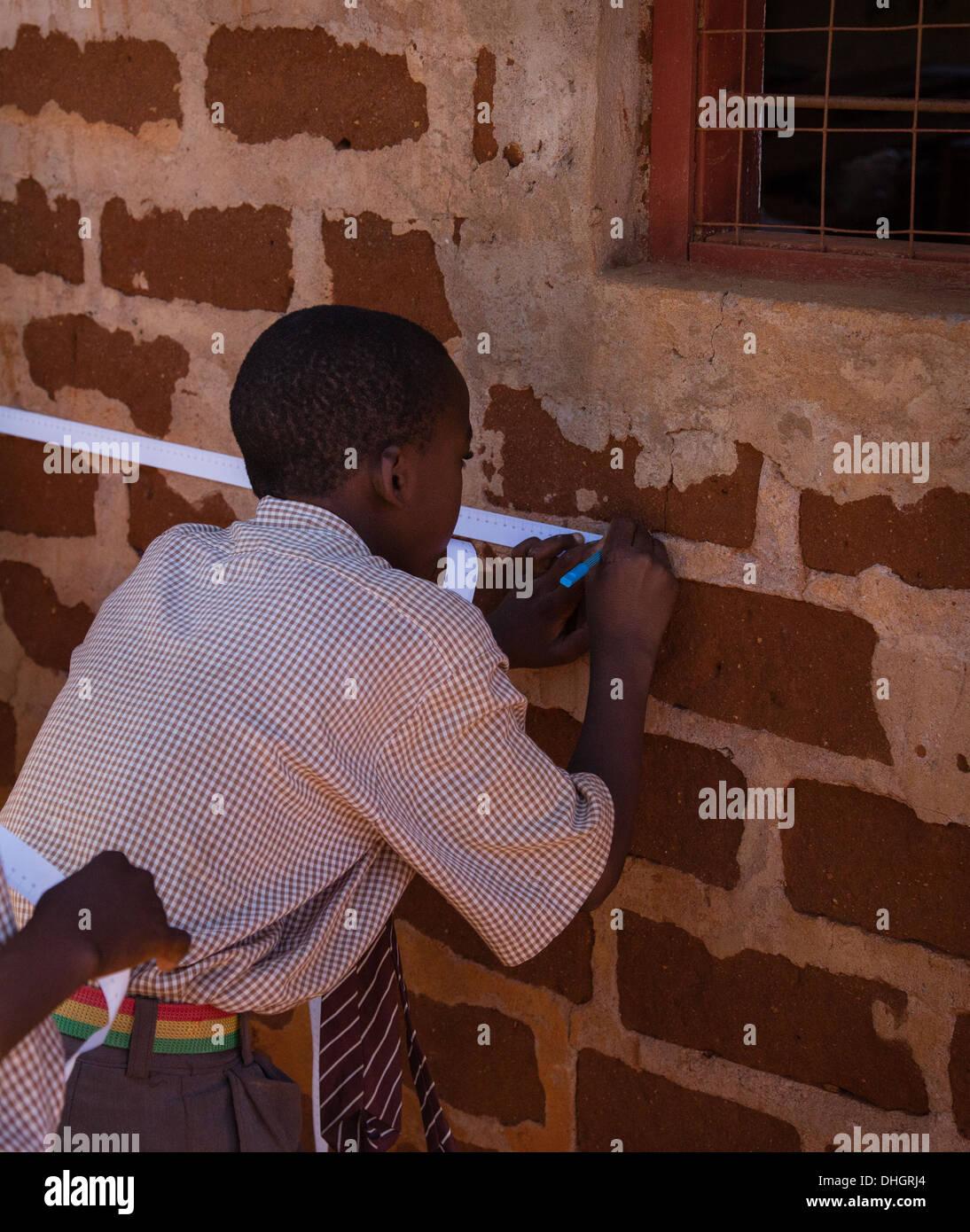 Un écolier mesures un mur extérieur d'une salle de classe avec un ruban de papier dans une école primaire du Kenya Photo Stock