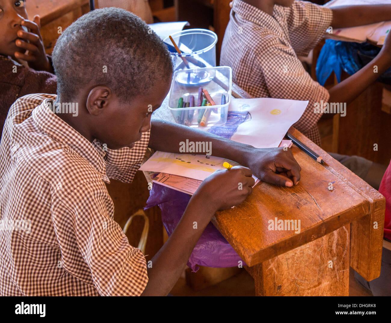 Un écolier dessin dans une classe d'art dans une école primaire dans le sud du Kenya Voi Photo Stock