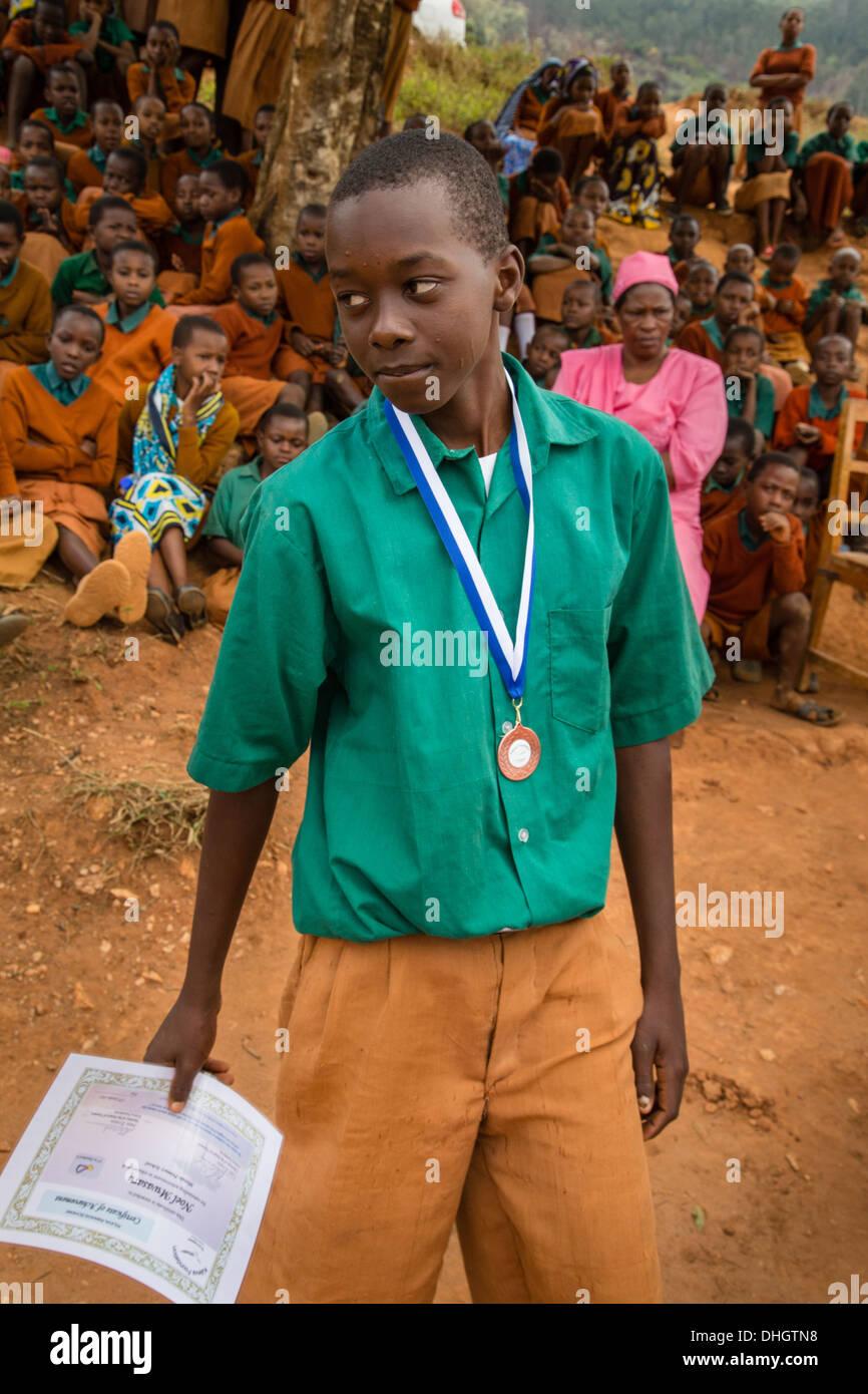 Écolier avec médaille et certificat de réussite dans une école primaire du Kenya dans les collines près de Sagalla Afrique Voi Photo Stock