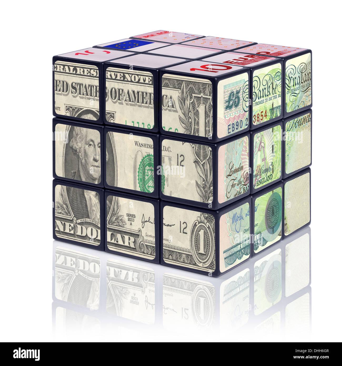 Un puzzle cube avec des billets en euros de chaque côté - avec le dollar américain, la livre sterling et l'Euro. Photo Stock