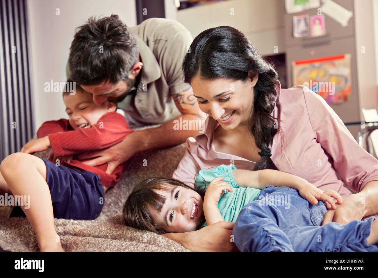 Famille avec deux enfants jouant sur canapé Photo Stock