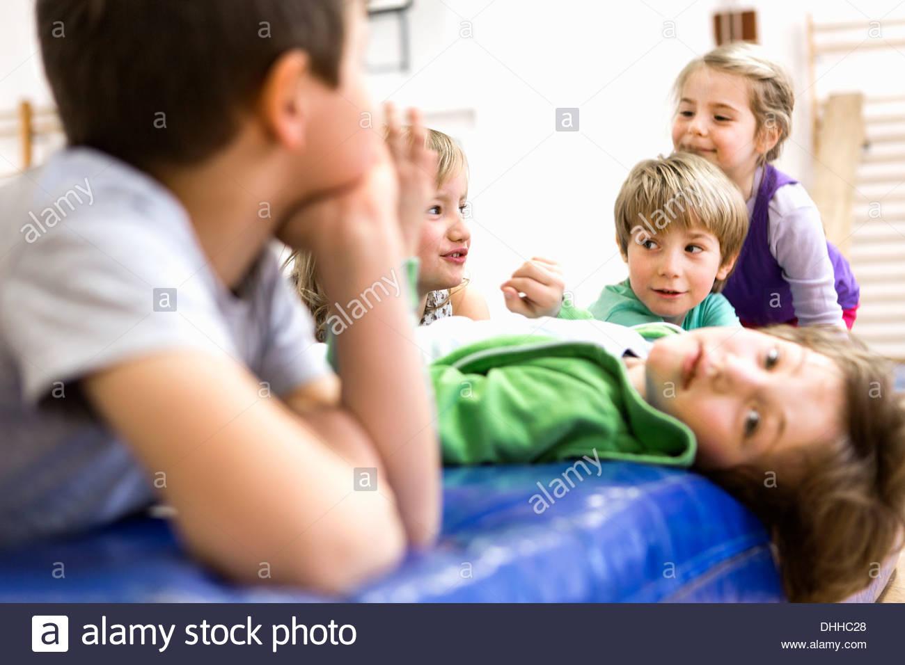 Des enfants assis et allongé sur des tapis d'entraînement Photo Stock