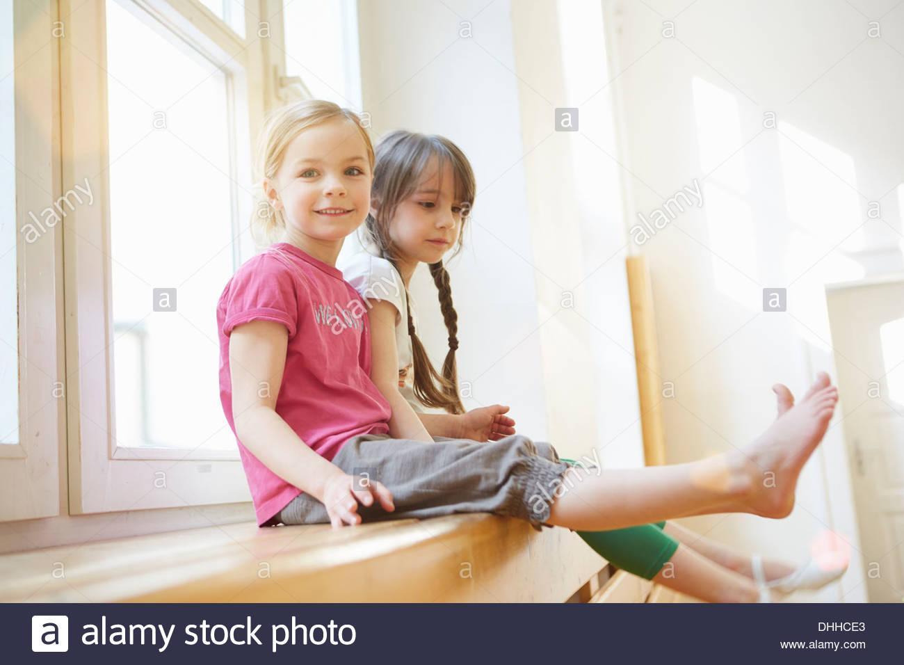 Les filles assis sur appareils en salle d'école Photo Stock