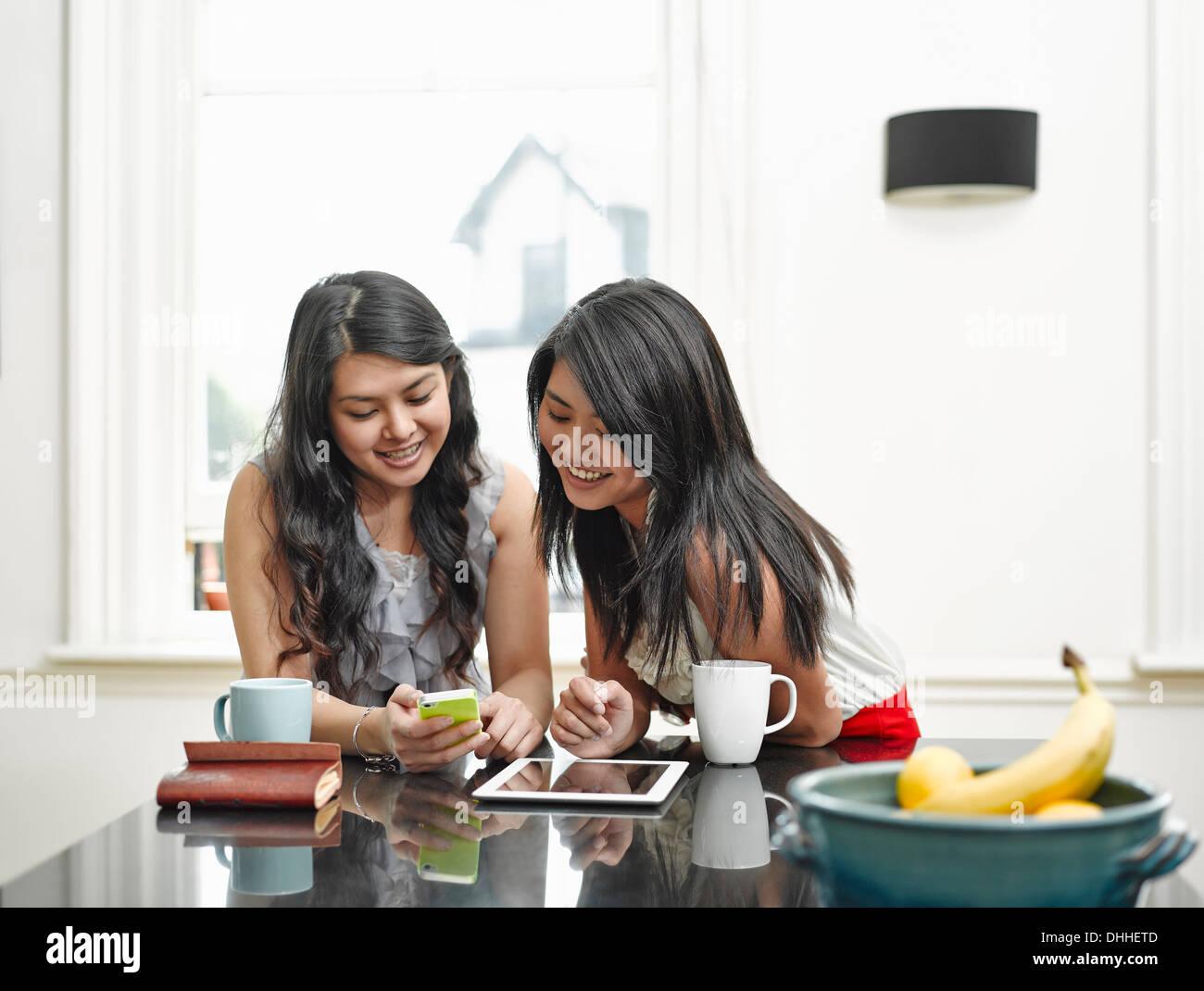 Deux jeunes femmes looking at mobile phone au comptoir de la cuisine Photo Stock