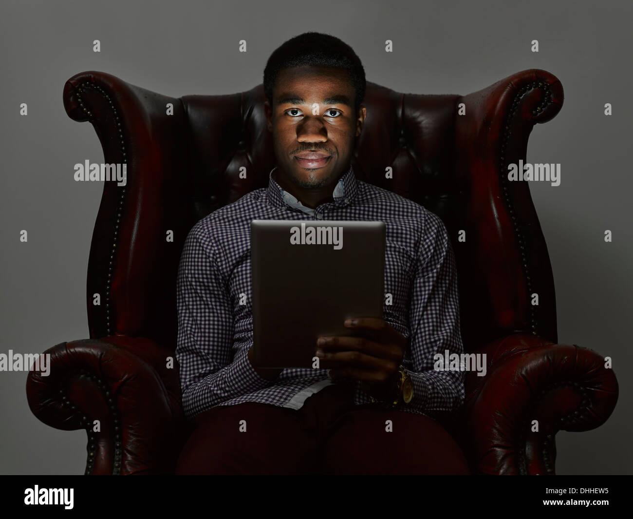 Portrait de jeune homme sinistre en fauteuil avec tablette numérique Photo Stock