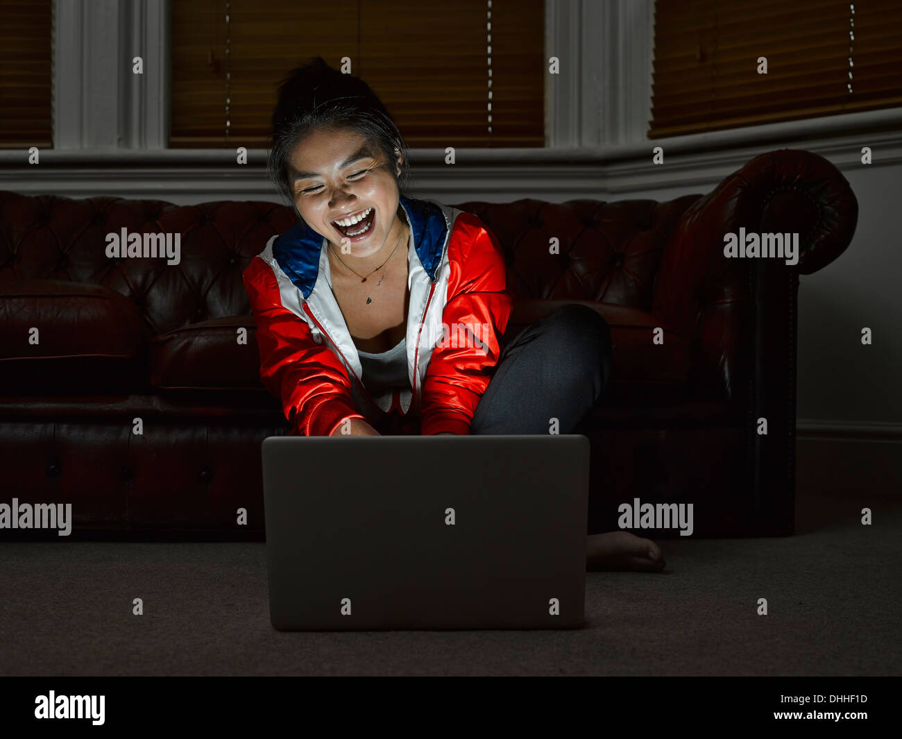 Young woman sitting on floor laughing at digital tablet Photo Stock