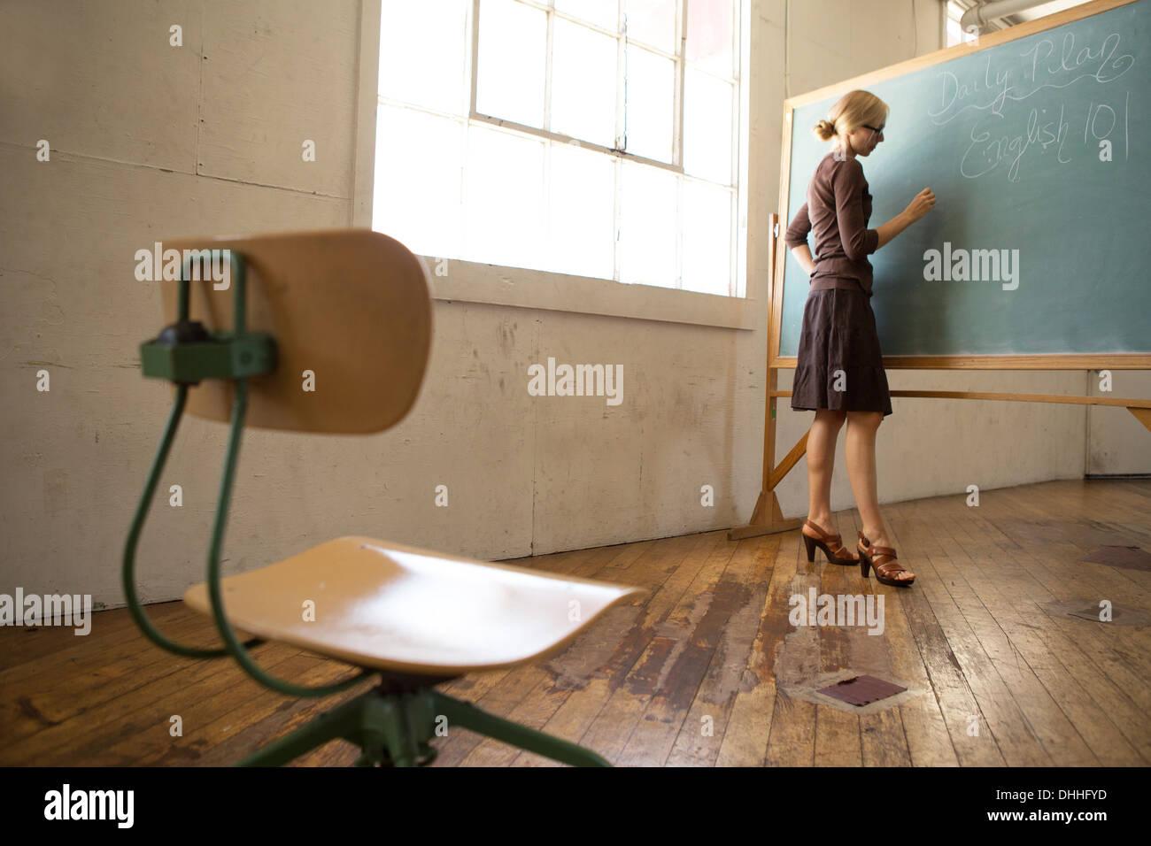 Teacher writing on blackboard with chaise vide en premier plan Photo Stock