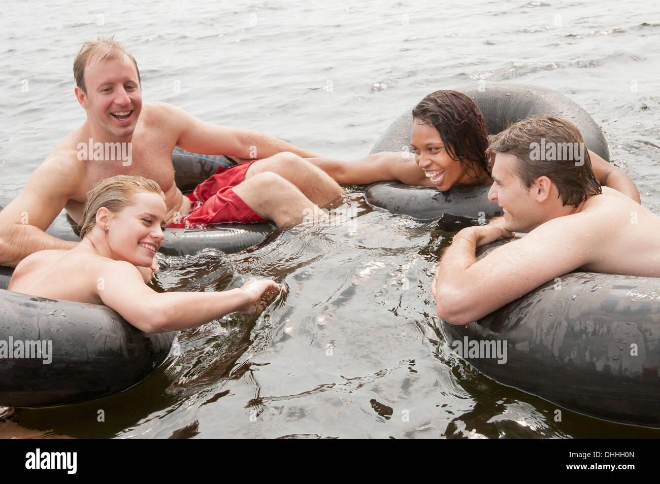 Les amis flottant dans les anneaux gonflables Banque D'Images