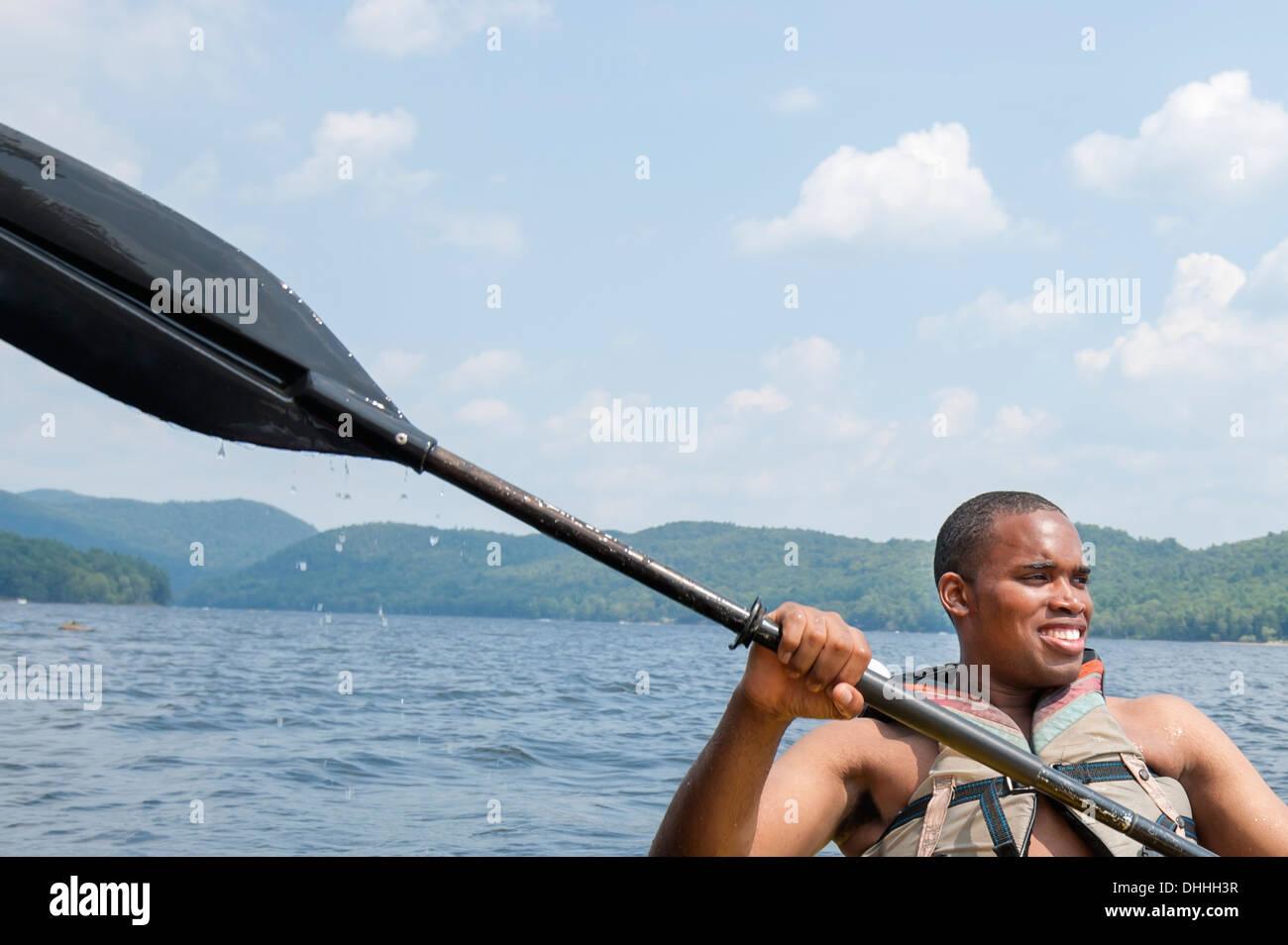 Jeune homme portant gilet holding oar Photo Stock
