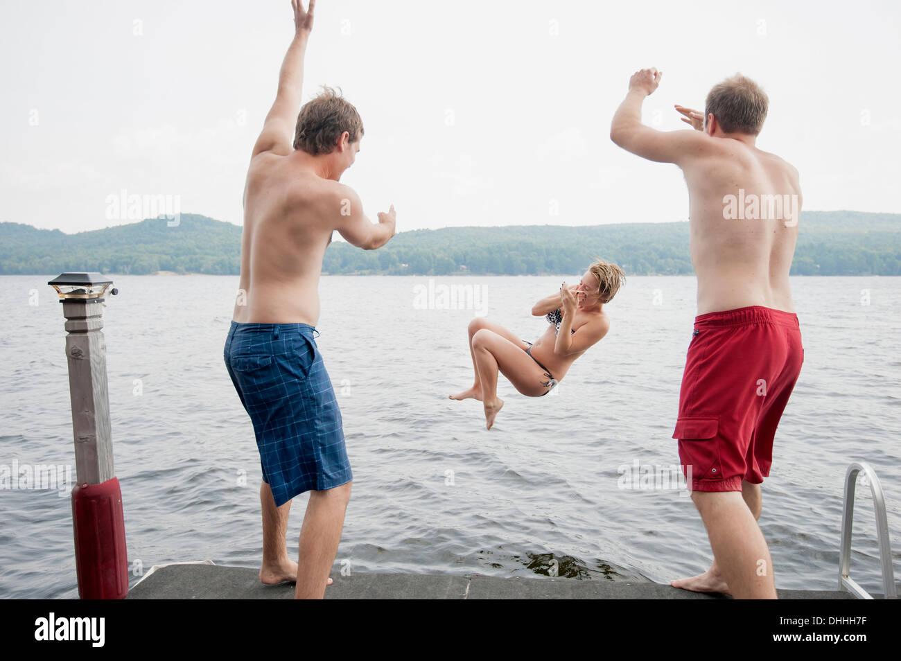 Jeter les hommes jeune femme jetée au large dans le lac Photo Stock