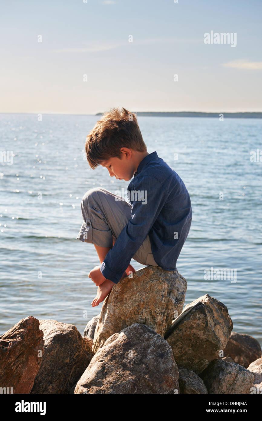 Garçon assis sur des rochers, Utvalnas, Suède Photo Stock