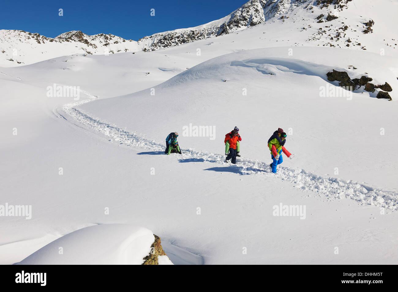 Les amis donnant à chaque autre piggy dos dans la neige, Kuhtai, Autriche Photo Stock