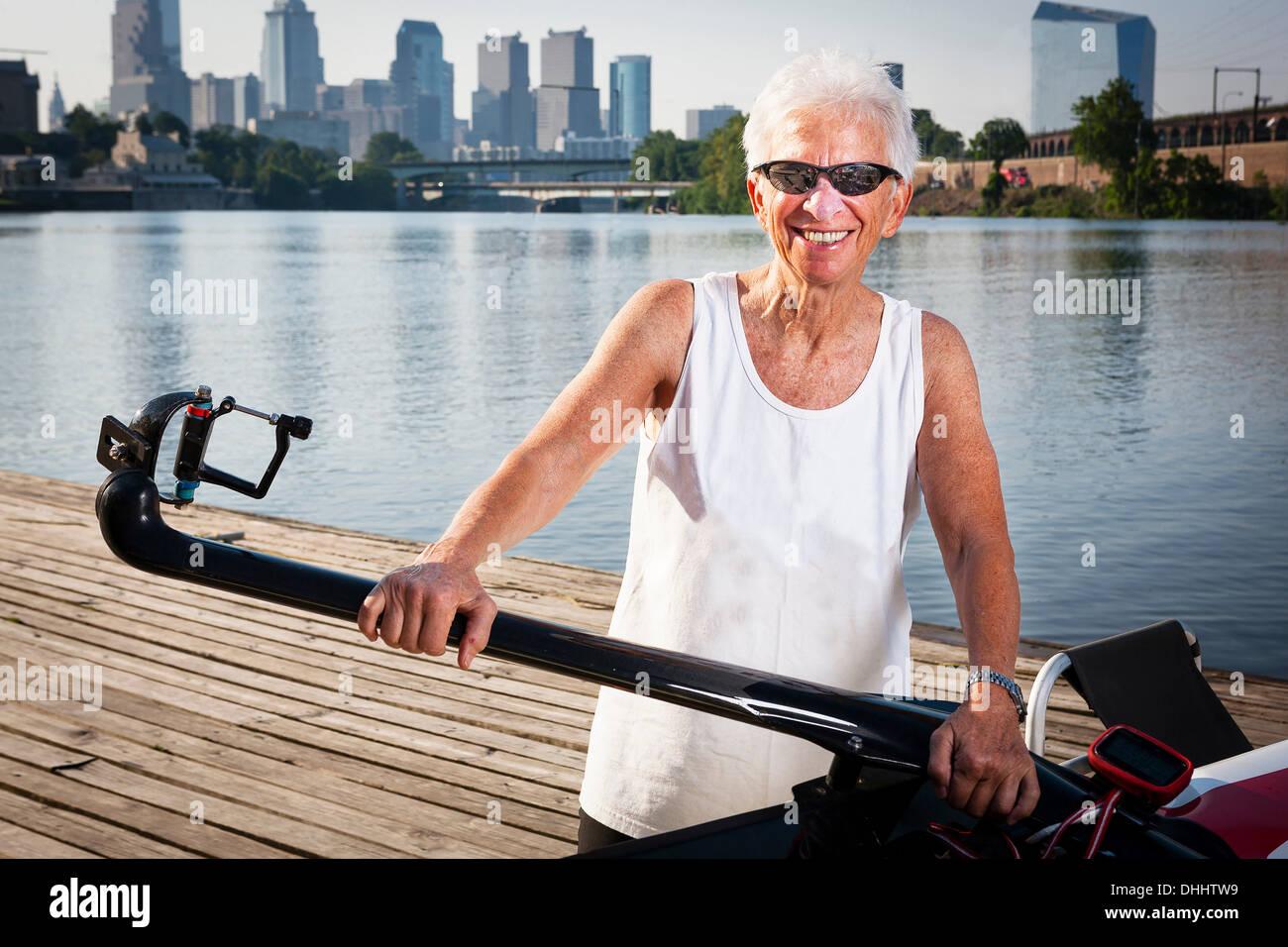 La rameuse sur jetée avec bateau à rames Banque D'Images