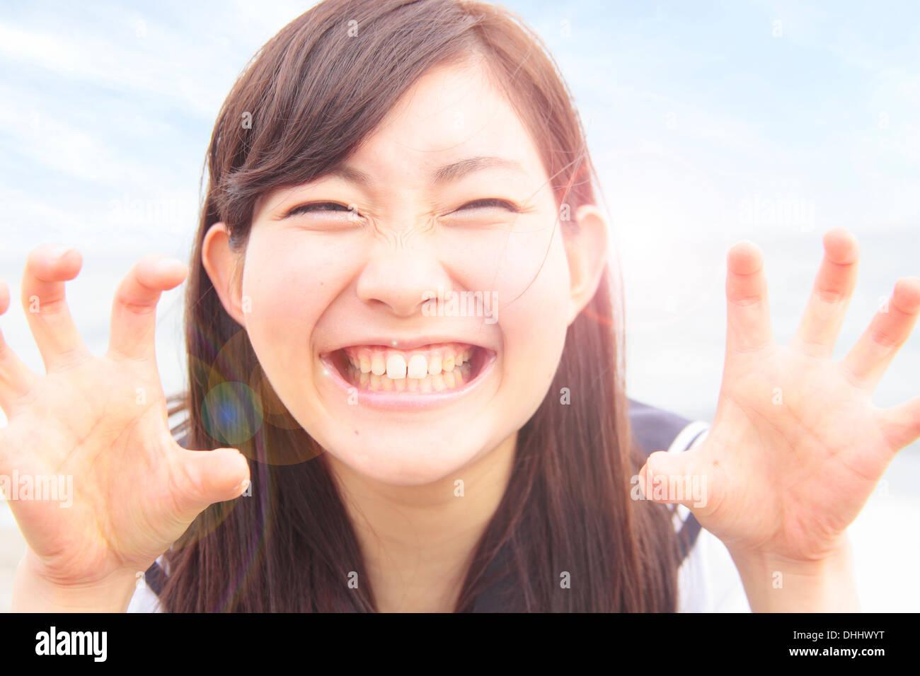 Young woman pulling funny face et des mains comme des griffes Photo Stock