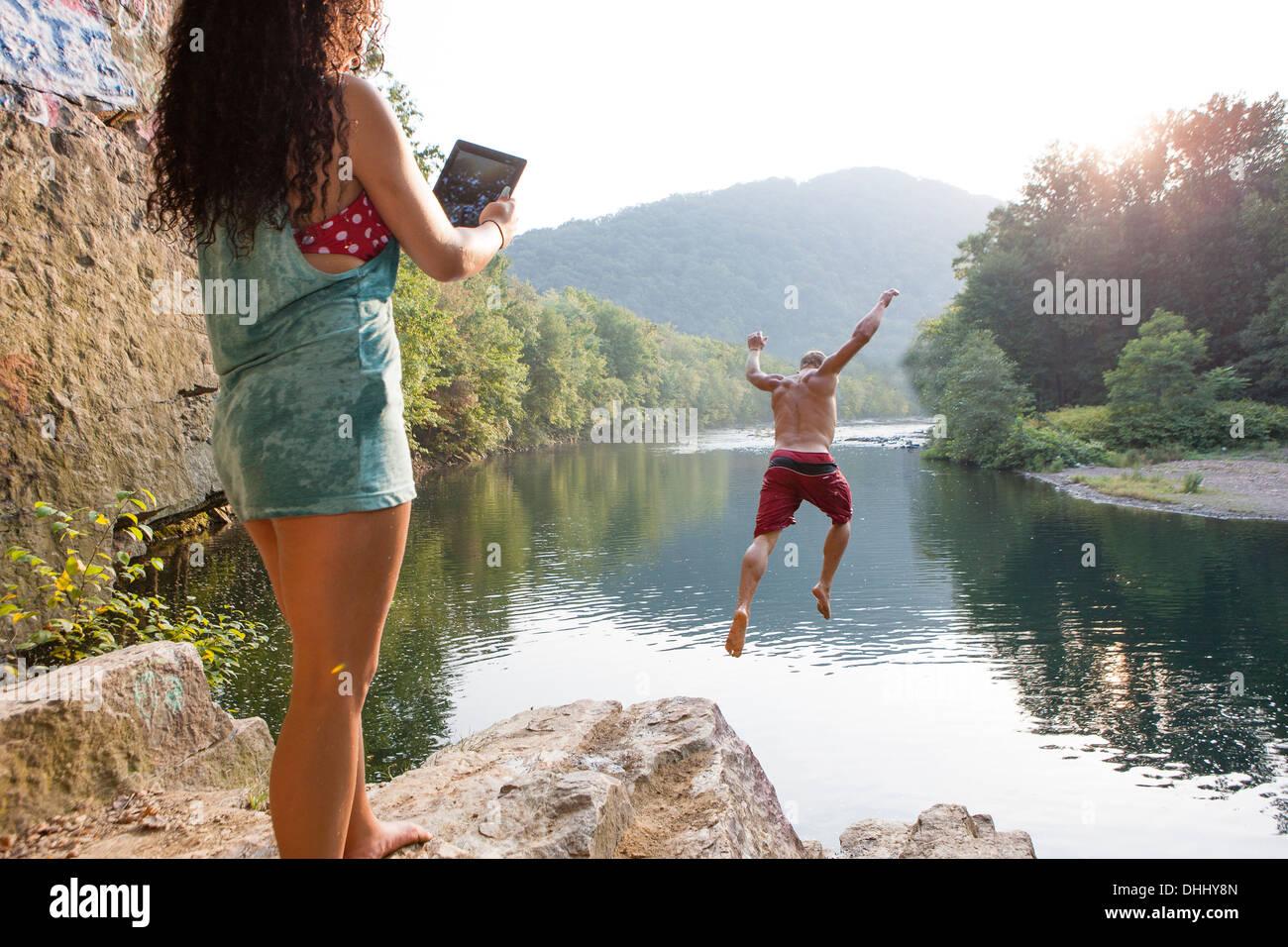 Femme photographiant copain sautant d'rock ledge, Hamburg, New York, USA Banque D'Images