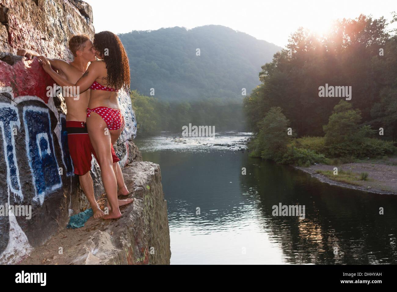 Jeune couple partageant un baiser sur rock ledge, Hamburg, New York, USA Photo Stock