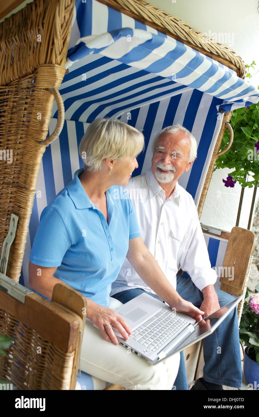 Couple de retraités à l'aide de l'ordinateur portable sur le siège de jardin Photo Stock