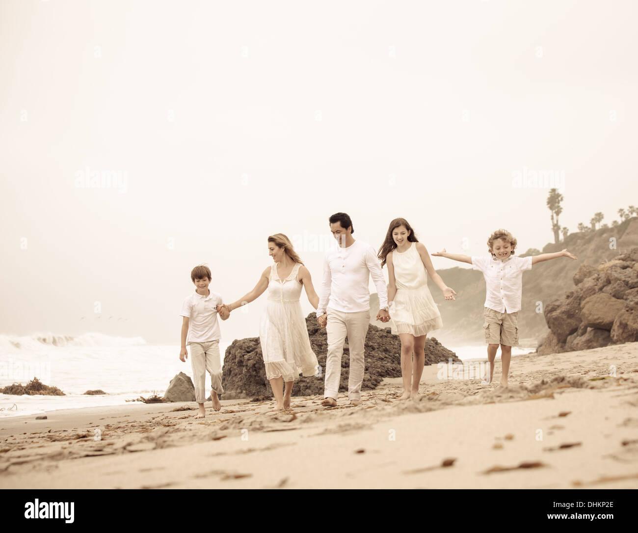 Beau jeune famille marcher sur la plage de Malibu en Californie Photo Stock