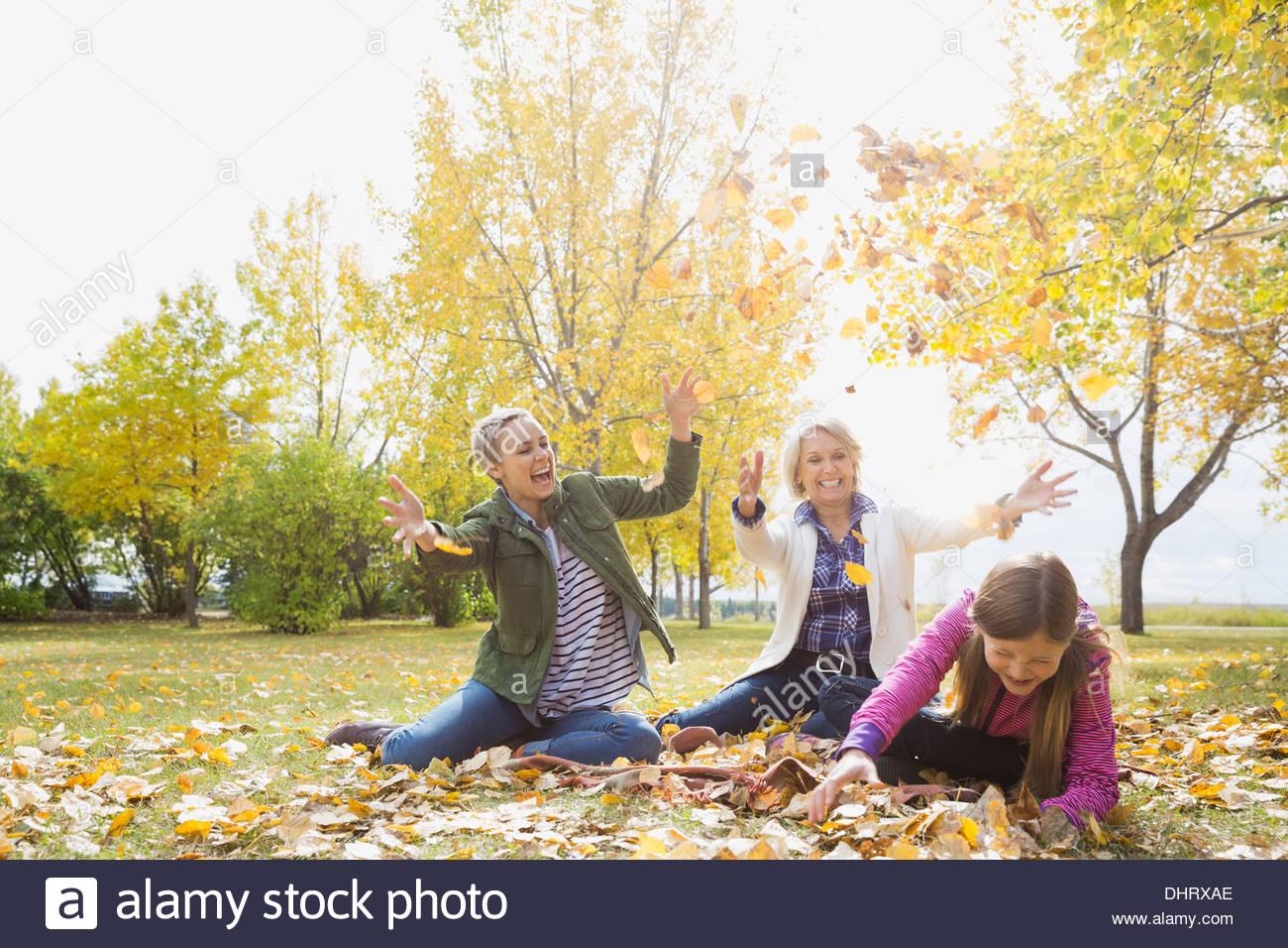 Trois générations de femmes jouant avec les feuilles d'automne dans le parc Photo Stock