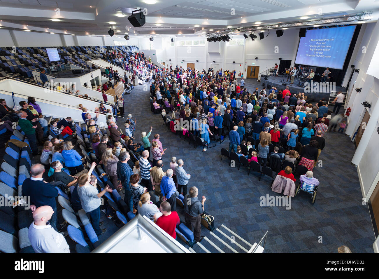 Congrégation participant au culte contemporain de la musique pendant le culte de dimanche à l'intérieur de la grande église moderne Kings Community. Photo Stock