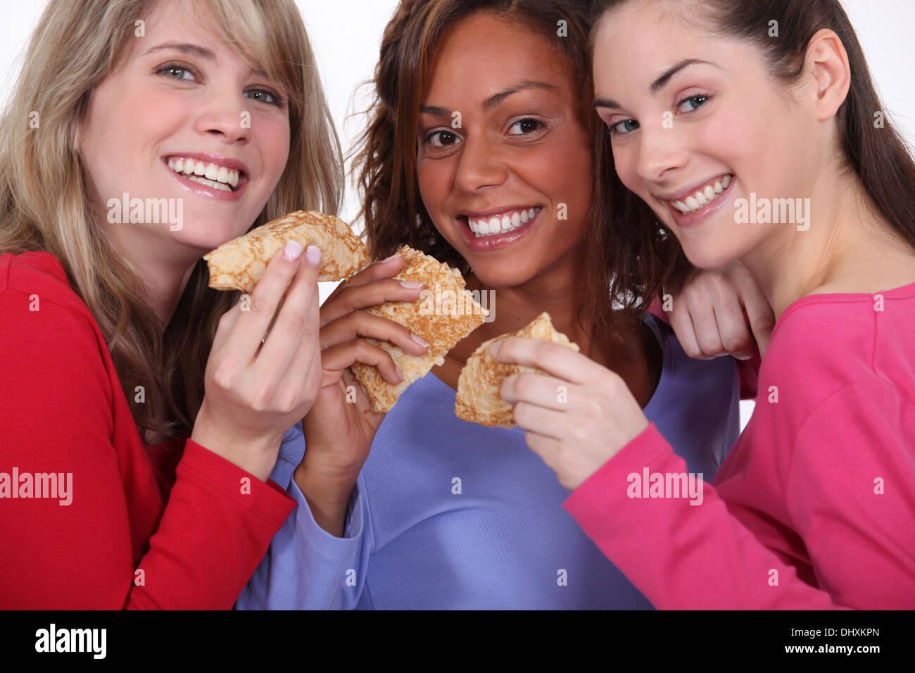 Trois amis de manger des crêpes Banque D'Images