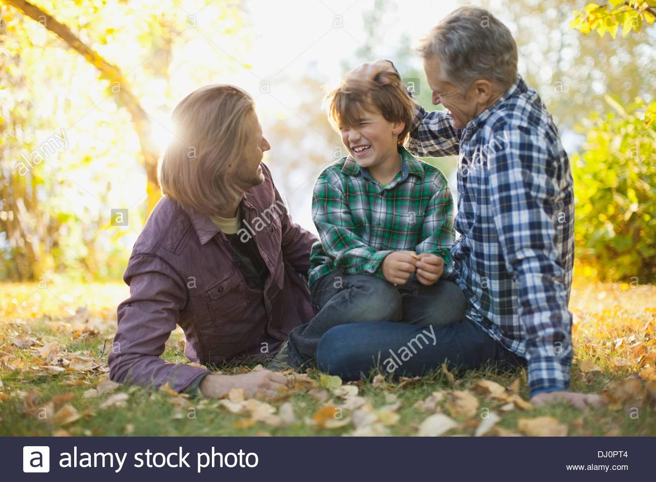 Trois hommes gais génération dépenses loisirs at park Photo Stock