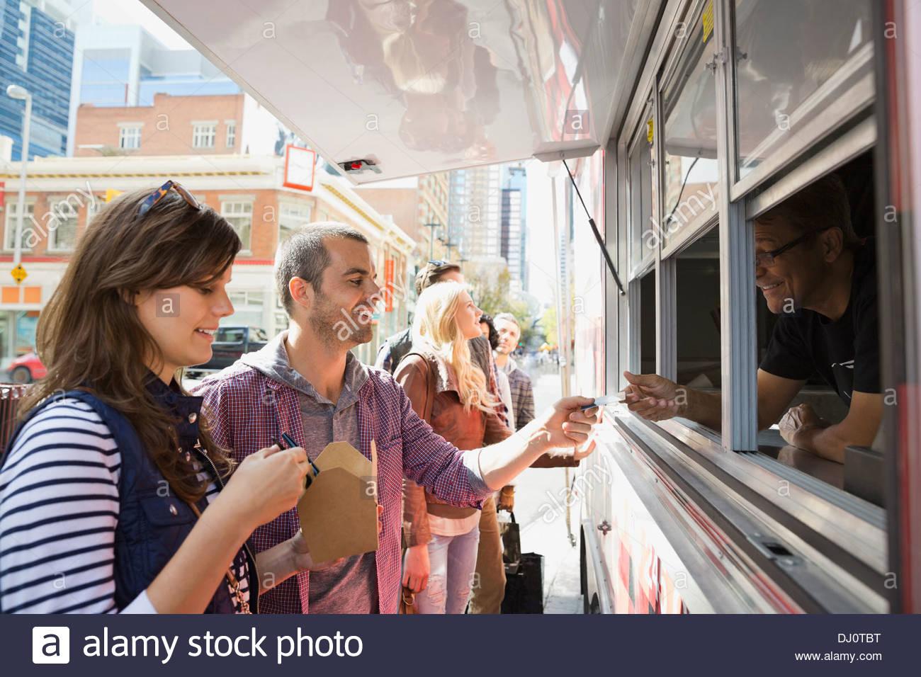 Couple de payer pour la nourriture à emporter Photo Stock